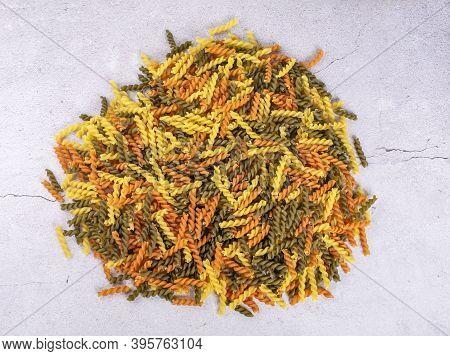 Dry Pasta Fusilli. Fusilli Have Spiral Shape And Yellow , Green, Orange Color. Pasta Is Delicious It