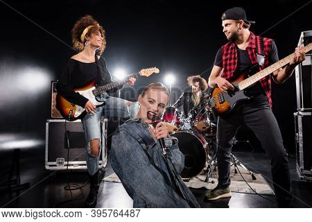 Kyiv, Ukraine - August 25, 2020: Female Vocalist Singing In Microphone While Sitting Near Guitarists