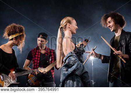 Kyiv, Ukraine - August 25, 2020: Blonde Vocalist Talking With Drummer Standing Near Musicians Playin