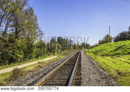 View Of Train Tracks Fading Into The Distance And Green Grass And Blue Skies
