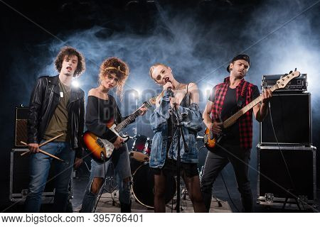 Kyiv, Ukraine - August 25, 2020: Vocalist Of Rock Band Singing Near Musicians With Bass Guitars And
