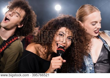Rock Band Vocalist With Microphone Singing Near Musicians With Backlit On Blurred Background