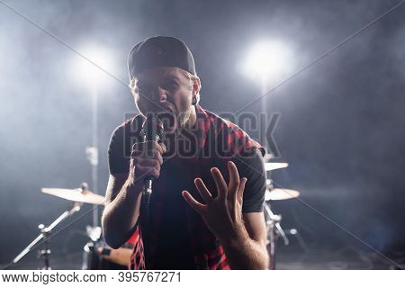 Rock Band Vocalist Screaming While Holding Microphone On Blurred