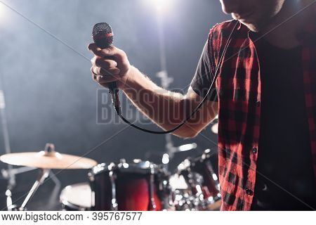 Cropped View Of Vocalist With Microphone With Blurred Drum Kit