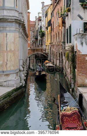 A Narrow Canal Between Houses, An Arched Bridge, A Gondola And Boats On The Water. Marble Wall Of Th