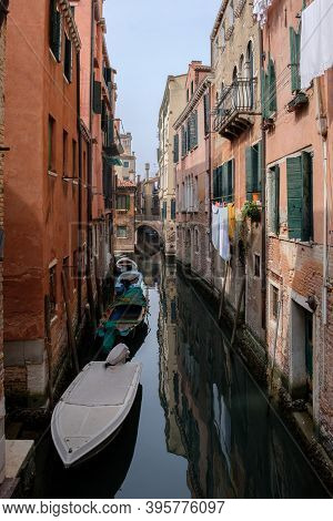 Narrow Canal Between Houses, Arched Bridge, Boats On The Water. Venice, Italy.
