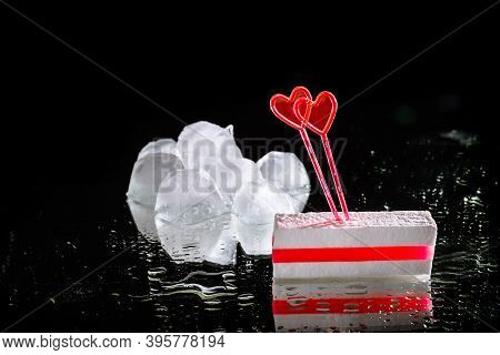 White Sugar Candy With Layer Of Red Marmalade And Two Heart Shaped Skewers. Melting Ice Cube On A Bl