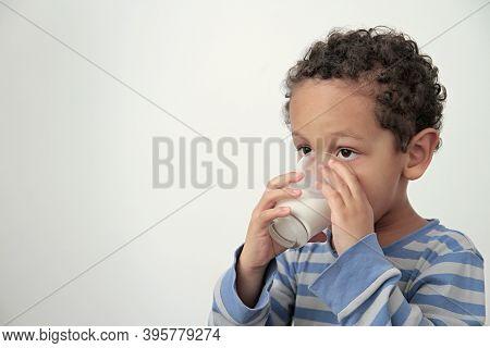 Boy Drinking Milk For Breakfast On White Background Stock Photo