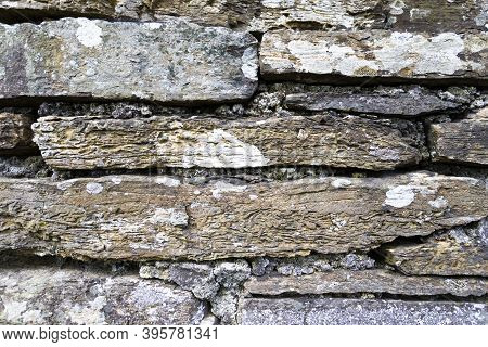 The Image Shows A Rustic Natural Stone Wall In Daylight