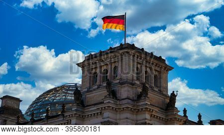 The Reichstag Building, Seat Of The German Bundestag, With A Waving Flag Of The Federal Republic Of