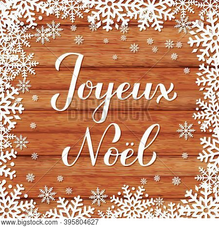Joyeux Noel Calligraphy Hand Lettering On Wood Background With Snowflakes. Merry Christmas Typograph