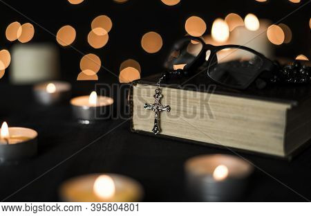 Rosary On Holy Bible With Candlelights And Bokeh Lights Background.