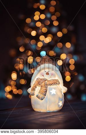 Beautiful Christmas Decoration. Festive Still Life. Nice Little Snowman Candlestick on the Table over Decorated Glowing Christmas Tree Background. Happy Winter Holidays at Home.