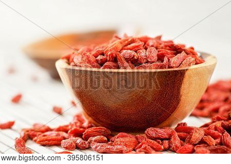Dried Goji Berries In Small Wooden Bowl, Some Scattered Over White Boards Table Under