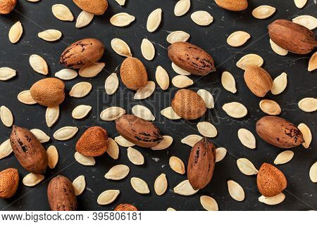 Whole Almonds, Pecan Nuts And Pumpkin Seeds Mixed On Black Marble Like Board, View From Above