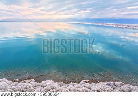 Salt Crystals Covering Sand Shore Of Dead Sea, Calm Clear Water Surface Near, Typical Morning Scener