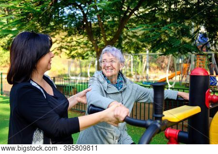 A Happy Old Woman Gets Onto A Fitness Outdoor Machine. A Caretaker Assists Her.