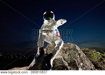 Front View Of Astronaut Pointing At Something While Resting On Top Of Rocky Hill Under Fantastic Blu