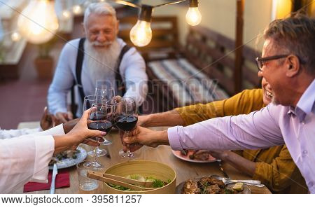 Happy Multiracial Senior Friends Toasting With Red Wine Glasses Together On House Patio Dinner - Eld