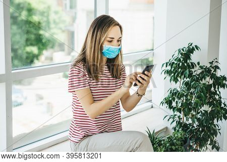 A Girl In A Protective Medical Mask Uses A Cell Phone.