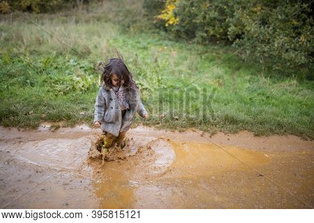 Happy Little Girl Joyfully Jumping And Splashing In A Muddy Puddle