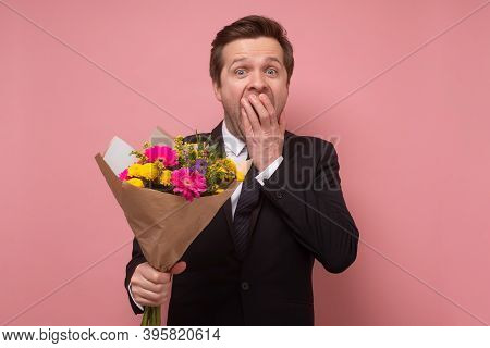 Smiling Man Holding A Bouquet Of Flowers Beong Shocked Or Surprise.