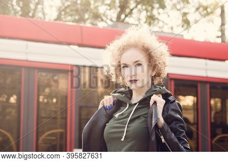 Portrait Of Fashionable Girl With Curly Hairstyle And Violet Lipstick Wearing A Rock Black Style Out
