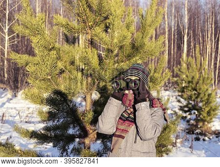 Young Woman Birdwatcher In Winter Clothes And Knitted Scarf Looking Through Binoculars In Winter Sno