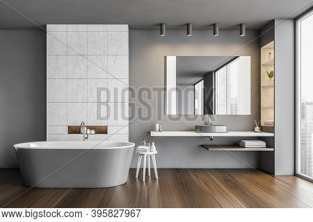 Dark Bathroom With Bathtub And Mirror With Sink Near Big Window. Grey And Wooden Design Of Minimalis