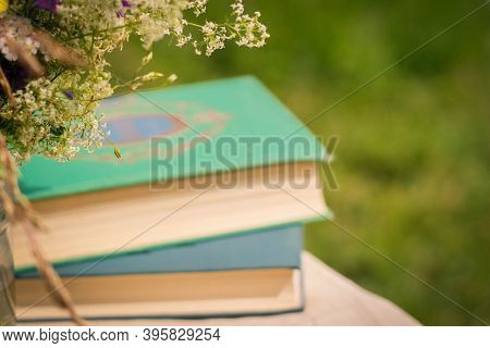 A Beautiful Bouquet Of Wildflowers And The Books On A Soft Green Background Of Summer Garden.