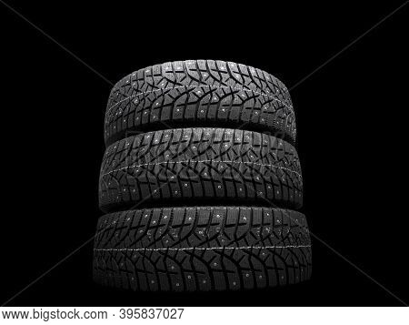 Winter Studded Tire. Winter Car Tires Isolated On Black Background. Tire Stack Background. Tyre Prot