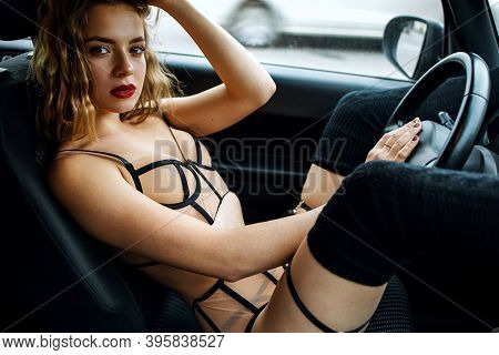Sexy Young Blonde Woman Sitting In Car