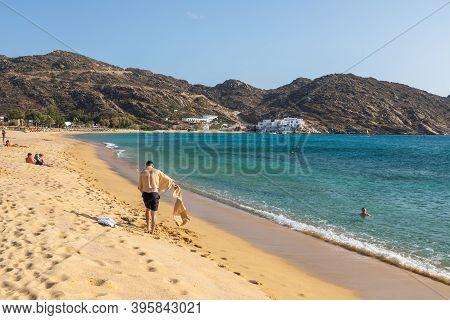 Mylopotas Beach, Ios Island, Greece- 20 September 2020: People Bathing In The Sun On The Beach And S