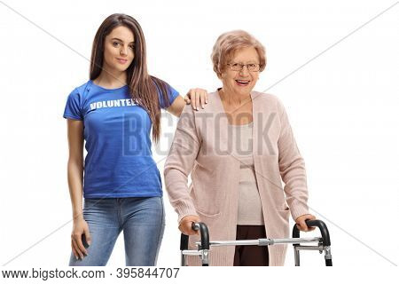 Young volunteer helping a senior lady with a walker isolated on white background
