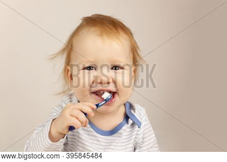 Little Baby Practicing Brushing Teeth On His Own. Kid With Red Hair Brushes Teeth. Oral Hygiene.