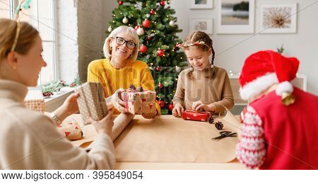 Delighted Women And Children Wrapping Christmas Presents Together While Gathering At Table At Home A