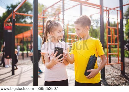 Caucasian Children Teenagers Use Cell Phone In Workout At Street Gym. Diverse Twins Watching Video L