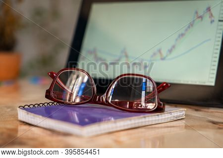 Close-up Photo Of An Glasses On A Notebook. There Is A Tablet Screen Out Of Focus With A Graphic, In