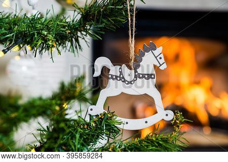 Wooden Christmas Decoration In The Shape Of White Horse With The Flame Of Fireplace In Background