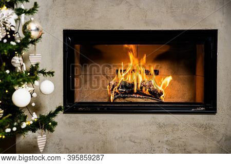 Builted Fireplace In The Wall With Flame By The Christmas Tree