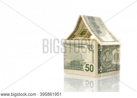 House made of money isolated on white background. Investment, real estate, property insurance, rental and housing concept.