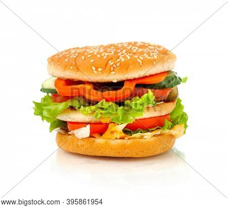Big appetizing burger, hamburger with vegetables close-up side view isolated on white background