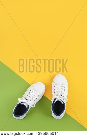 White Sports Shoes, Sneakers With Shoelaces On A Green And Yellow Background. Sport Lifestyle Concep