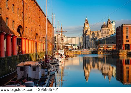 The Three Graces viewed from Royal Albert Dock with historical buildings and reflection in England, United Kingdom.