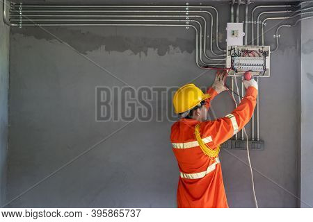 Asian Electrician Wear Safety Clothes With Electric Screwdriver Installations And Wires On Relay Pro