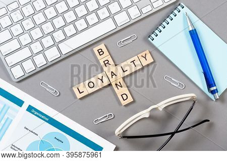 Brand Loyalty Concept With Words From Cubes. Still Life Of Office Workplace With Crossword. Flat Lay
