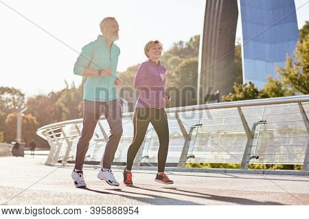 Healthy Mind And Body. Cheerful Active Mature Couple In Sportswear Smiling While Running On A Sunny