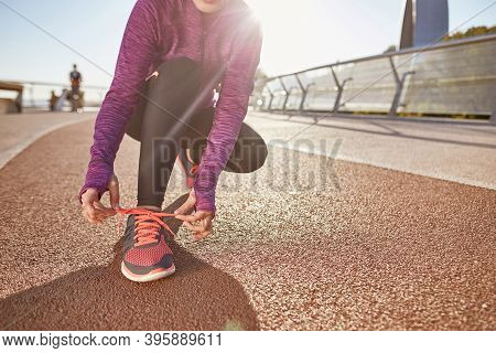 Preparation. Cropped Shot Of Active Mature Woman Wearing Sportswear Tying Her Shoelaces While Gettin