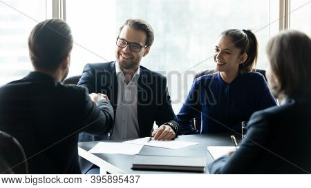 Smiling Businesspeople Shake Hands At Team Briefing