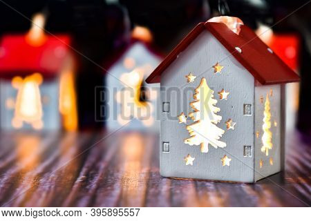 Small Christmas Houses With Christmas Tree Windows That Glow From The Inside. Christmas Garland In T